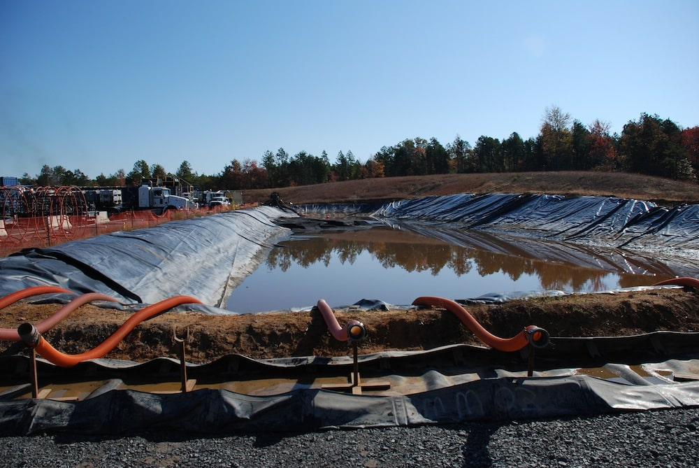 A water impoundment at a drill pad in the Fayetteville Shale gas play of Arkansas. The water will be used in the hydraulic fracturing process, where it will be combined with chemicals and sand, then used to create artificial fractures in gas-bearing rocks to allow the gas to be recovered. Photo Credit: Bill Cunningham, USGS