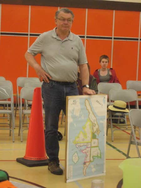 moderator of the table top exercise holding a map displaying Cortes Island's evacuation zones