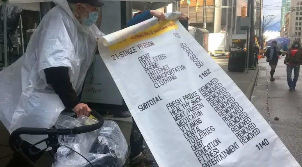 Myles Harps holds up a giant novelty receipt showing expenses for people like him who depend on B.C. disability assistance, at a 300ToLive rally which blocked Howe Street downtown near government offices, demanding an end to below-poverty rates last Thursday, March 18