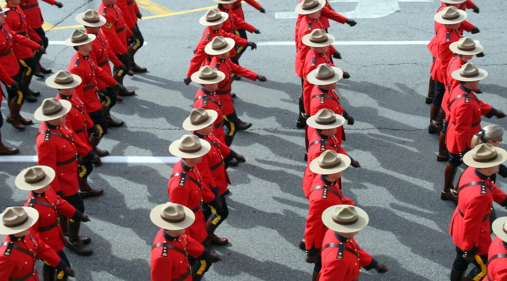 Several rows RCMP officers, dressed in red coasts and stetsons, marching down a road marching