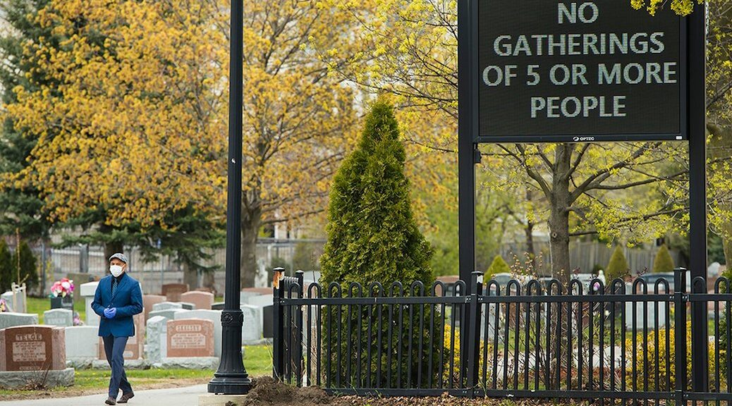 A man leaves an Ontario cemetery in May 2020. A new report claims the number of Canadians who died of COVID-19 could be twice as high as reported.
