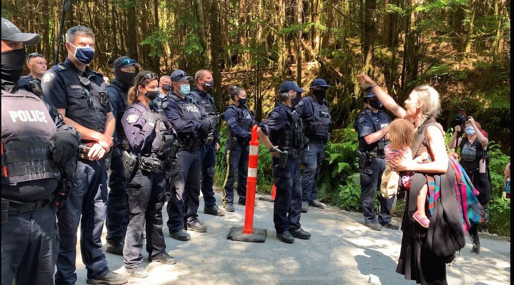 Woman with a child in her arms, gesturing defiantly in front of more than a dozen police who are suited up for confrontation. gesturing