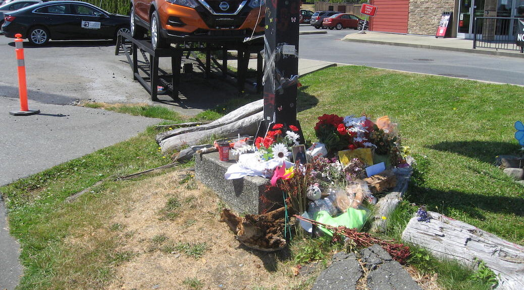 A photo of Jared Lowndes, flowers, posters and cards around the street lamp across from where Jared Lowndes was killed
