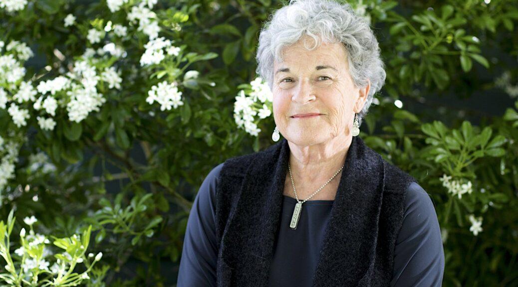An elderly woman beside bushes