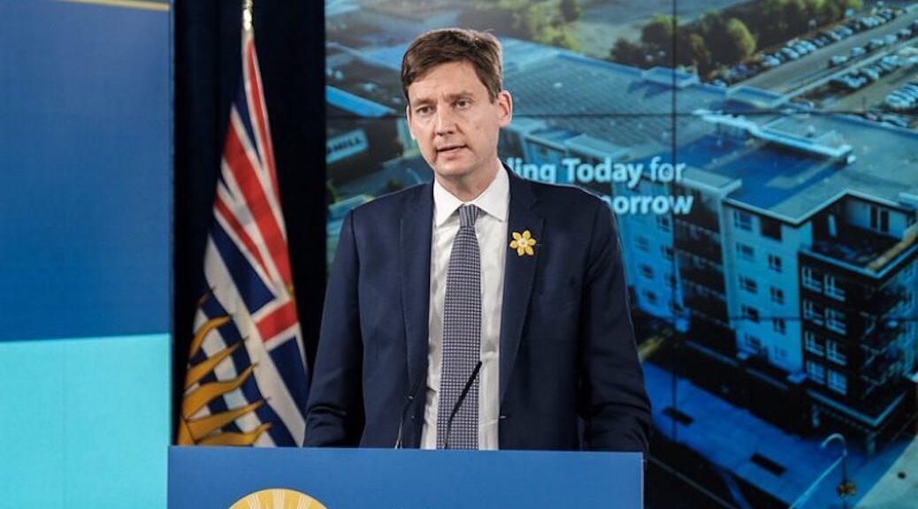 Man speaking at podium, BC flag behind him