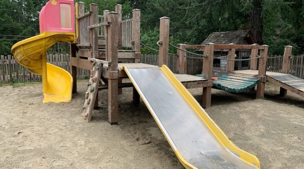 A playground, with a slide, fort and other stuff