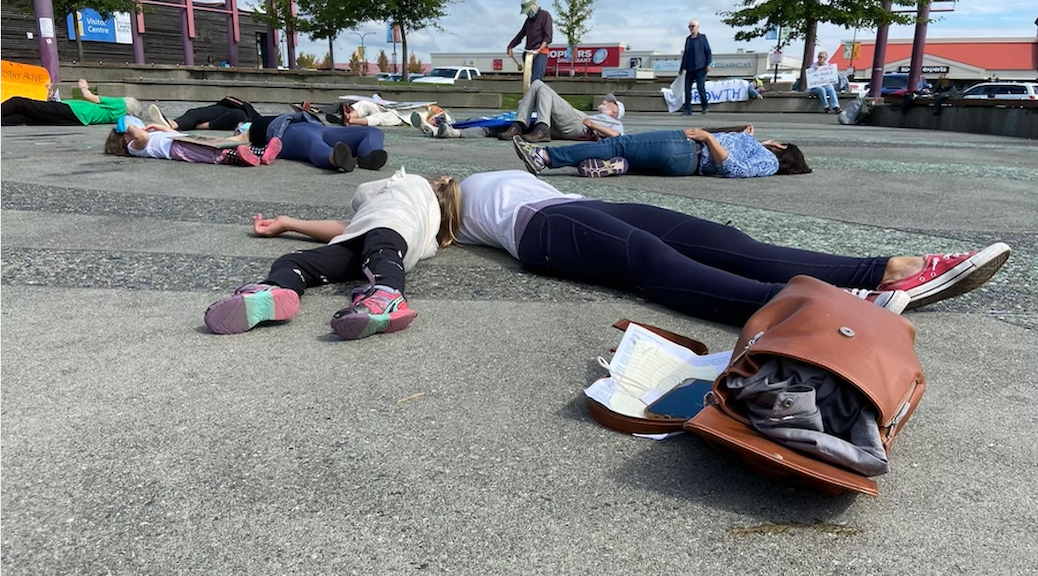 A half a dozen people lay upon the tiles of a city square as if dead. Two others look on.