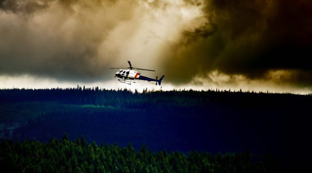 helicopter flying over a forest, smoke from a wildfire rises up